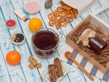 Transparent cup of black tea, crackers, jam and lemon on a wooden table. Large cup of black tea, lemon, jam jar and crackers on an old wooden table in French Royalty Free Stock Photography