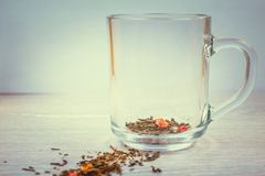 Transparent Cup and dry tea leaves on table background royalty free stock photography