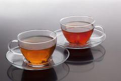 Transparent cup with green and black tea Royalty Free Stock Photos