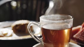 Transparent cup of hot black tea and breakfast on the blurred background on the wooden table , morning time. Transparent mug of hot black tea and teasty stock video footage