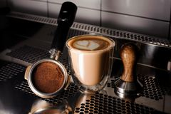 Transparent cup of hot coffee and barista essentials. Beautiful transparent cup of a delicious hot coffee and different barista essentials standing on the steel Stock Images