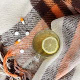 Hot beverage for a speedy recovery. Transparent cup of hot drink with lemon and drugs from the cold on warm plaid background royalty free stock images