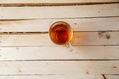 Transparent cup with a hot drink on light wooden background . View from above.  royalty free stock photography