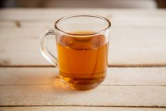 Transparent cup with a hot drink on light wooden background . View from above.  stock images