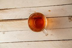 Transparent cup with a hot drink on light wooden background . View from above.  stock image
