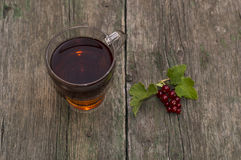 Transparent cup of tea and branch of red currant on a shabby tab Stock Photo