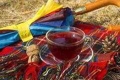 Transparent cup of tea on checkered scarf and umbrella Royalty Free Stock Photography