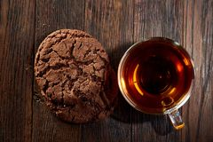 Cup of tea with a couple of chocolate cookies on a wooden background, top view. A transparent cup of tea with a couple of chocolate cookies on a a dark wooden Royalty Free Stock Photos