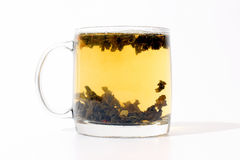 Transparent cup of tea with custard on white background
