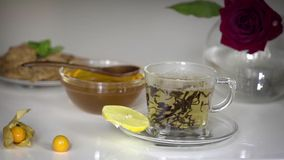 Transparent cup of tea with honey. Transparent cup of large leaf black tea with honey and lemon on white background stock footage