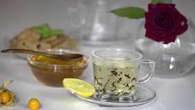 Transparent cup of tea with honey. Transparent cup of large leaf black tea with honey and lemon on white background stock video