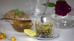 Transparent cup of tea with honey stock video footage