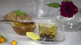 Transparent cup of tea with honey. Transparent cup of large leaf black tea with honey and lemon on white background stock video footage