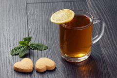 Transparent cup of tea with lemon, mint and cookies on a wooden Stock Image