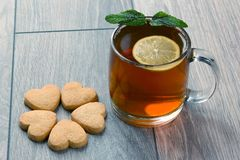 Transparent cup of tea with lemon, mint and cookies on a wooden Stock Photos