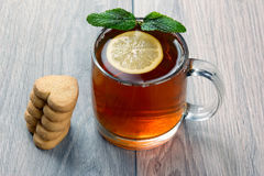 Transparent cup of tea with lemon, mint and cookies on a wooden Stock Images