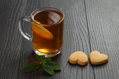 Transparent cup of tea with lemon, mint and cookies on a wooden Royalty Free Stock Photos