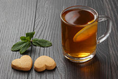 Transparent cup of tea with lemon, mint and cookies on a wooden Stock Photography