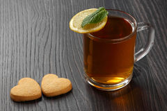 Transparent cup of tea with lemon, mint and cookies on a wooden Stock Photo