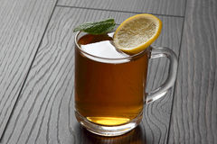 Transparent cup of tea with lemon, mint on a wooden table Royalty Free Stock Photography