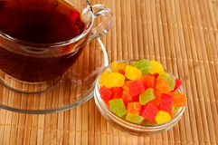 Cup of tea with candied fruits. Transparent cup of tea with reflection on a bamboo serviette Stock Photography