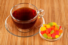 Cup of tea with candied fruits. Transparent cup of tea with reflection. Candied fruits Royalty Free Stock Image
