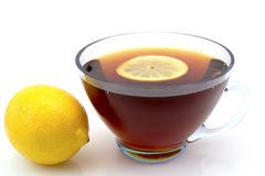 Transparent cup of tea with a slice of lemon and whole lemon left isolated on white Royalty Free Stock Photos