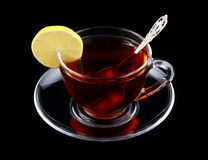 Transparent cup of tea with spoon and lemon. Isolated on black Stock Image