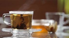 Transparent cup of tea on the table. A cup of tea on the table stock video footage