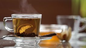 Transparent cup of tea on the table. A cup of tea on the mirror table stock footage