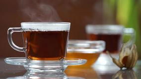 Transparent cup of tea on the table. A cup of tea on the white table. Blurred background stock video