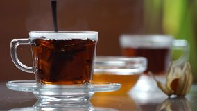 Transparent cup of tea on the table stock video