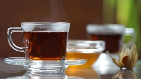 Transparent cup of tea on the table. A cup of tea on the white table. Blurred background stock video footage