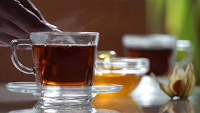 Transparent cup of tea on the table. A cup of tea on the white table. Honey spoon takes. Blurred background stock video