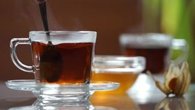 Transparent cup of tea on the table. A cup of tea on the white table. Honey spoon takes. Blurred background stock video footage