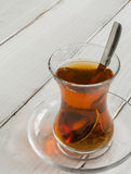 Transparent cup of thin glass and black tea. Spoon. Stock Image