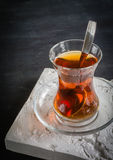 Transparent cup of thin glass and black tea. Spoon. Royalty Free Stock Photos