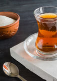 Transparent cup of thin glass and black tea. Spoon. Royalty Free Stock Image