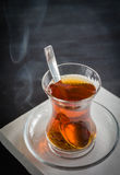 Transparent cup of thin glass and black tea. Spoon. Stock Photography