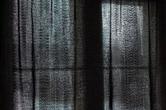 Closeup of a black, translucent curtain closed in front of a window royalty free stock photography