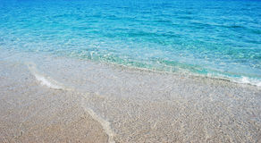Transparent deep blue wave of the sea that breaks on the shore w. Ith white foam as background royalty free stock photo