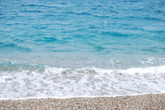 Transparent deep blue wave of the sea that breaks on the shore w. Ith white foam and sand for summertime Stock Photo