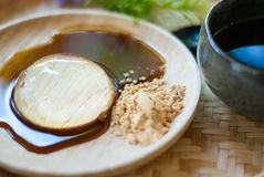 Transparent dessert, Mochi, is on wooden plate, with sweet sauce. And some sugar Stock Image