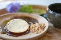 Transparent dessert, Mochi, is on wooden plate, with sweet sauce. And some sugar Royalty Free Stock Image