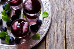 Transparent drink blueberries. Transparent drink made from blueberries in a glass on a wooden background. Selective focus Stock Image