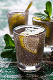 Transparent drink in a glass. With chia seeds, lemon and mint on a wooden background. Selective focus Royalty Free Stock Images