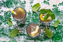 Transparent drink in a glass. With chia seeds, lemon and mint on a wooden background. Selective focus Royalty Free Stock Image