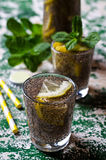 Transparent drink in a glass. With chia seeds, lemon and mint on a wooden background. Selective focus Stock Image