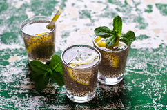 Transparent drink in a glass. With chia seeds, lemon and mint on a wooden background. Selective focus Royalty Free Stock Photos
