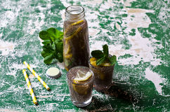 Transparent drink in a glass. With chia seeds, lemon and mint on a wooden background. Selective focus Stock Photos
